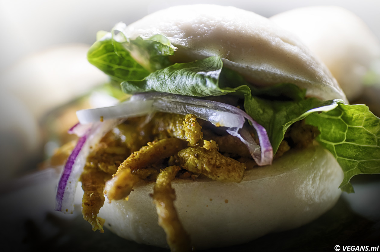Vegan Vietnamese Veggie Shwarma Banh served as 2 Cloudy banh filled with vegetarian shawarma made of wheat protein, spiced with curry, red onion, and fried white onion. a dressing of Picante black bean paste, tarragon, chili, scallion, and coriander.